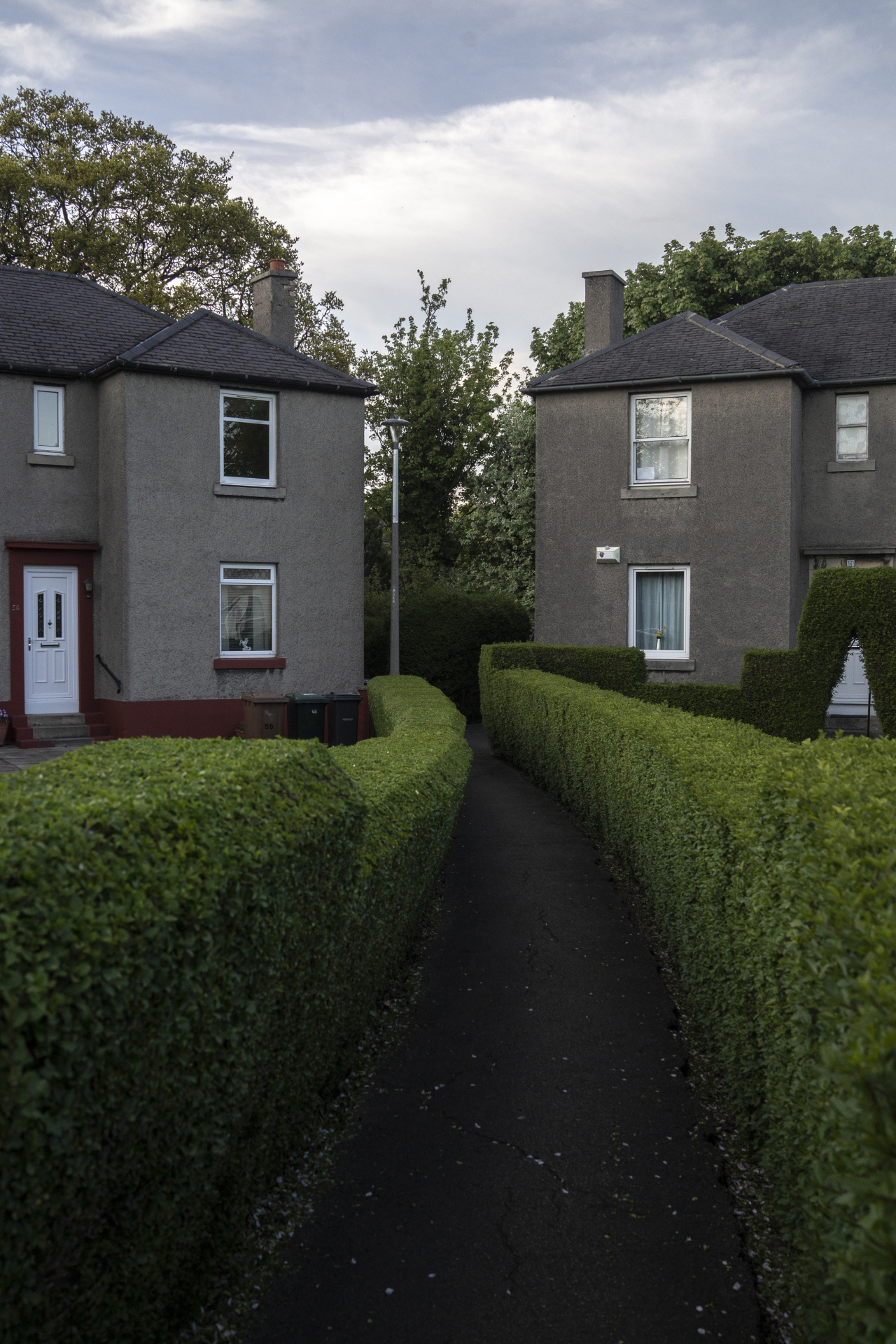 Kieran Dodds Photography Down the Line podcast, July 2020 An avenue of hedges between houses in Warriston, Edinburgh.   At a time of national crisis, the humble border hedge took on a renewed sense of purpose, its presence a vivid metaphor for self-isolation and social distancing. This series of suburban landscapes began n March 2020 during the permitted daily lockdown excursions in the 'bungalow belt'  of Edinburgh. Green space in cities brings many benefits for citizen's mental and physical health. As well as privacy, border hedges provide cover for nesting birds and reducing wind shear to give shelter to plants.