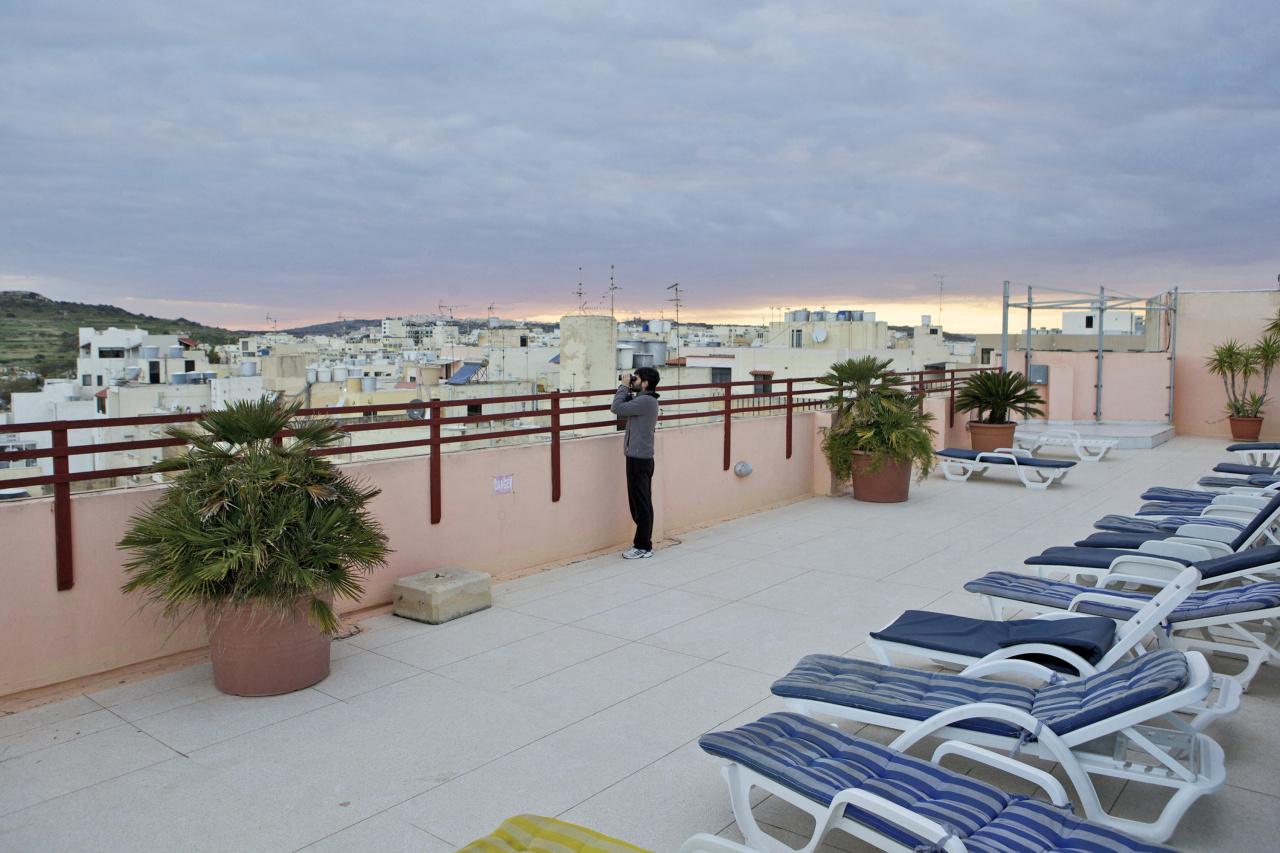 Kieran Dodds Deadly skies over Malta, May 2012 A volunteer keeps watch from the top floor of the Bella Vista hotel in Bugibba.  Spring Watch Malta is a conservation camp run by BirdLife Malta's  In 2012, fifty volunteers from across Europe coverged in a tourist hotel in Bugibba, north Malta, to track migrating birds and monitor any illegal spring hunting by the 11,000 permitted hunters.  Under EU leglislation, Spring hunting is illegal but the Maltese government, which joined the EU in 2004, allows hunting of turtle dove and quail.  Hunters regularly shoot other species including birds of prey which are made stuffed for private collection.