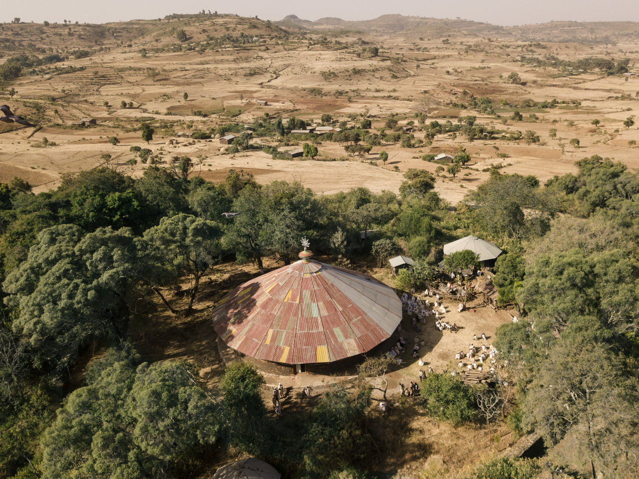Kieran Dodds World Photography Organisation: Hierotopia Interview Gebita Giyorgis Church surrounding by forest canopy with encroaching fields.  Church forest land surrounding churches have become islands of biodiversity in seas of agriculture, the last remnants of a once-expansive native cover. Conservation is a key tenet of the Tewahdo Ethiopian Orthodox which has protected them until now when these forests are threatened like never before as agriculture expands to cope with the country's booming population which is due to double over the next 30 years.